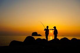 親子で夕日の中釣りをしている写真